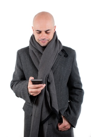 shaved head: Bald man with tweed coat and scarf using his smart phone smiling  Isolated
