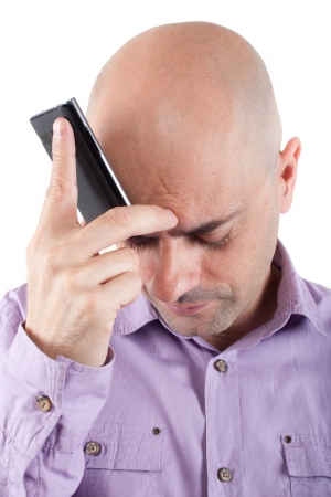 Worried bald man looking down with a cellphone supported in the forehead  Lilac shirt  Isolated  photo