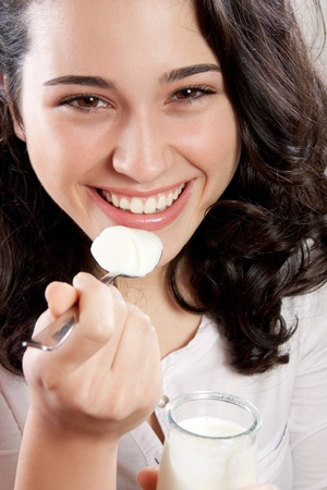 Closeup of a happy woman laughing while eating a yogurt  Looking at the camera