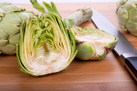 Cutting fresh artichokes on the board