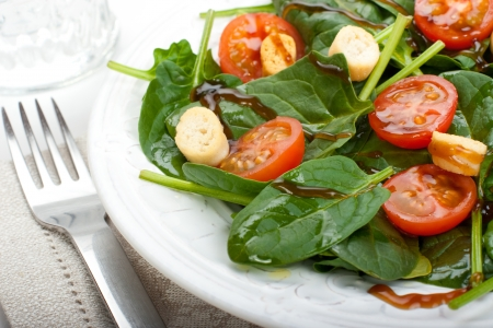 baby spinach: Salad of spinach, tomato cherry and croutons with olive oil and balsamic vinegar syrup  Glass of water at the background  Stock Photo