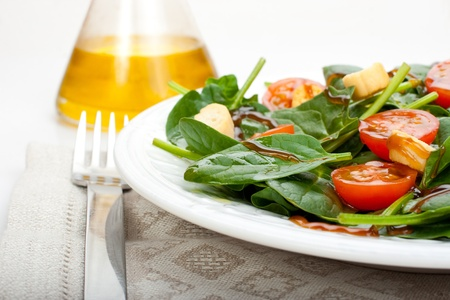 Salad of spinach, tomato cherry and croutons with olive oil and balsamic vinegar syrup  Glass oilcan at the background  Stock Photo