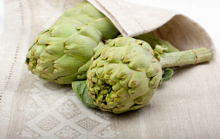 dishcloth: Three fresh artichokes on a dishcloth