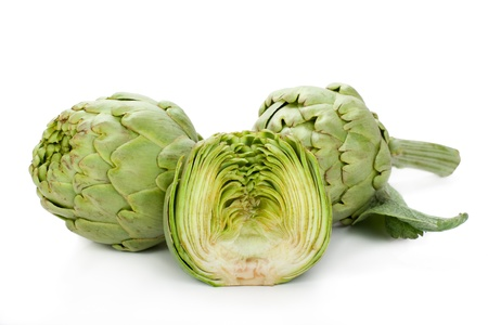 Two fresh artichokes with stem and leaf and a half showing the heart  Isolated  Stock Photo
