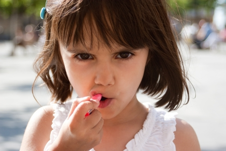 Concentrated little girl putting on lipstick with her hands full of crumbs and staring at camera  Outdoors and sunny