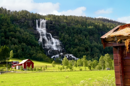 Farm next to a waterfall in Norway  In the foreground a traditional cottage with dry grass roof  Stock Photo