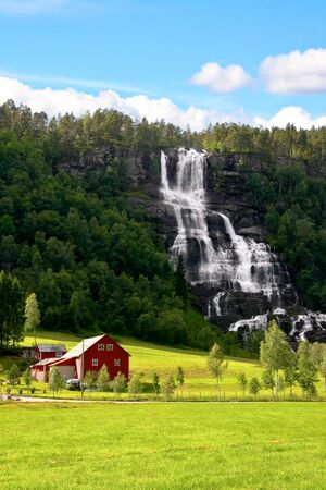 Traditional red farm next to a waterfall and green field in Norway Stock Photo - 18569682