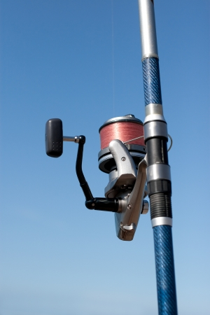 Close up of fishing reel in a fishing rod against a blue sky  Stock Photo