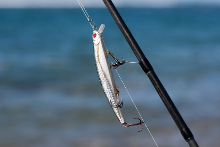 Silver fishing lure in fishing rod against the blue sea  Stock Photo