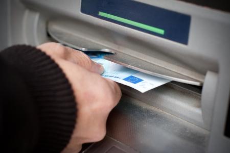 Man de hand krijgen 20 euro biljetten bij geldautomaat in de straat