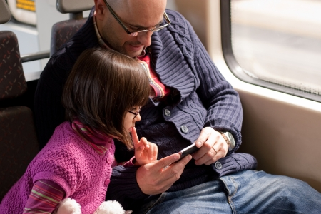 Father and daughter with glasses watching a video on the moile phone while traveling in train