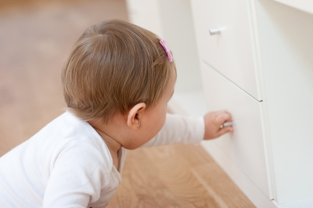 Baby girl opening a drawer with curiosity  Risks at home with little children  Soft focus  Stock Photo