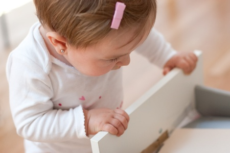 Baby girl looking inside a drawer with curiosity  Risks at home with little children  Focus in the eye
