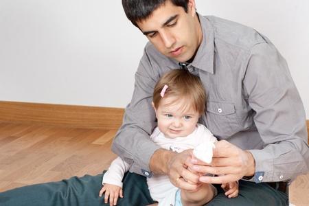 ni�os vistiendose: Padre concentrado vestir a su beb� en casa Foto de archivo