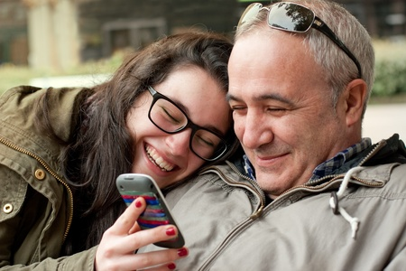 Father and teenager daughter with head in his shoulder sharing something funny in a mobile phone photo