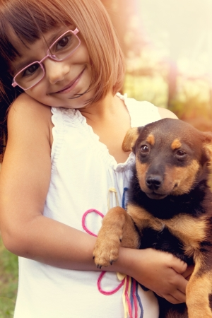 Happy little girl with eye glasses holding her puppy  Warm effect edition