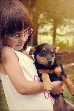 Happy little girl with eye glasses holding her puppy  Warm effect edition  photo