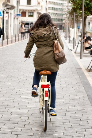 parka: Woman cycling down the street in a vintage bicycle  Back view