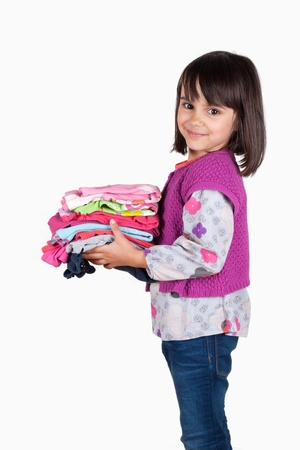 Happy little girl holding a stack of shirts