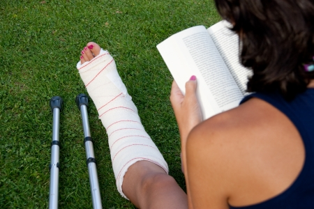 Woman with broken leg reading a book sitting in the grass photo