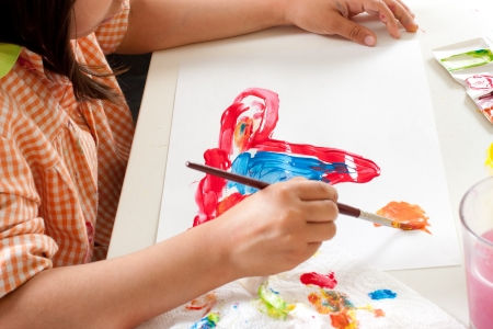 interior drawing: Hands of child painting with paintbrush Stock Photo