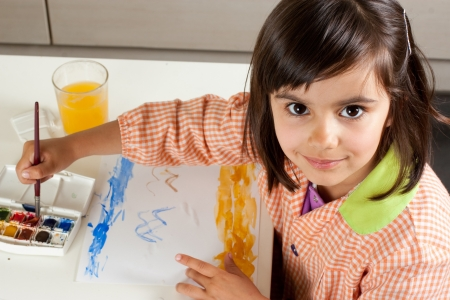 Cute little girl painting a landscape with watercolors  Looking at camera  photo