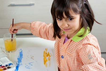 mischief: Cheerful little girl painting with watercolors Stock Photo