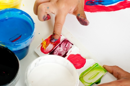 Hand of a child mixing colors with fingers for painting photo