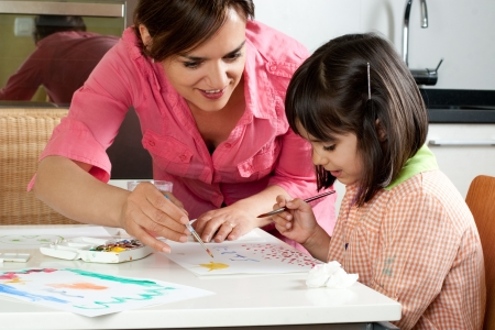 niños dibujando: Madre e hija que pintan juntos en casa con pinceles y acuarelas