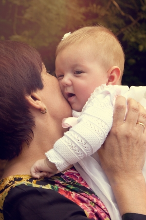 Grandmother holding and kissing tenderly her granddaughter  Warm effect edition