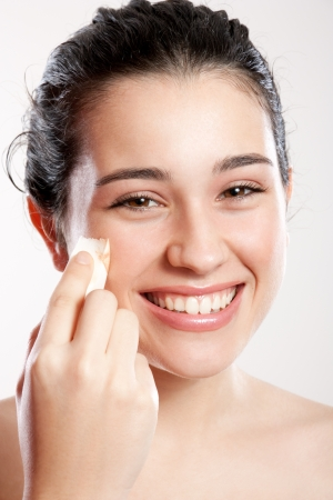 Happy and beautiful teenage girl applying foundation on face with a sponge photo