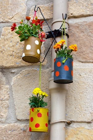 stones with flower: Hanging flowerpots made with cans in the street  Stock Photo