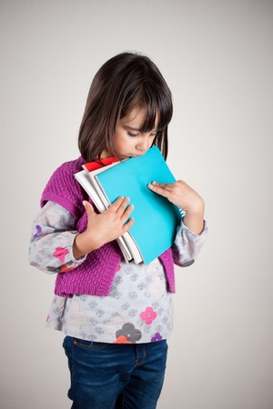Sad little girl loking down holding her new school books photo