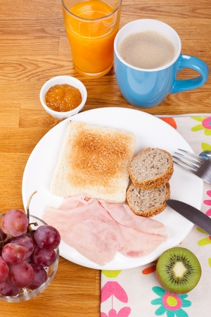 Full breakfast consisting of toast, jam, bread, cereal, ham, orange juice, grapes and kiwi photo