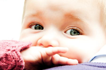 dentition: Close up of sad baby with hand in mouth with dentition pain over fathers shoulder Stock Photo