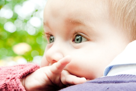Baby blue eyed discovering nature over father shoulder Stock Photo