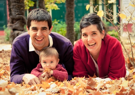 Happy family at the park in autumn lying in the fallen leaves