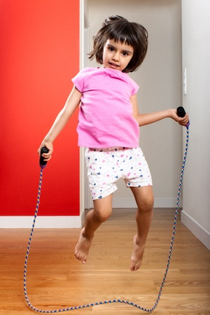 Little girl jumping rope at home photo