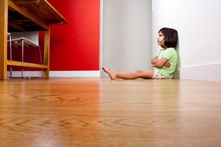 huffy: Bored and angry child alone sitting on the floor against the wall at home Stock Photo