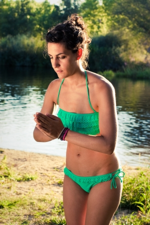 Young girl in bikini doing yoga next to a river at sunset greeting with palms together photo
