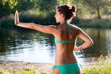 Young girl in bikini practicing tai chi next to a river at sunset photo