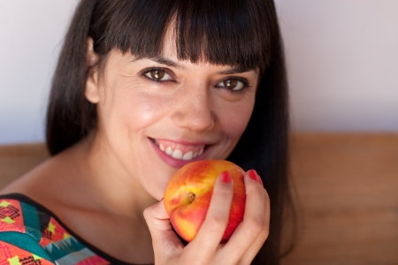 Closeup of a cute young woman holding a fresh nectarine
