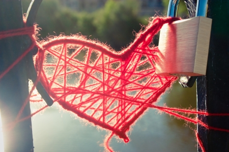 Heart of red wool and padlock on the railing of a river