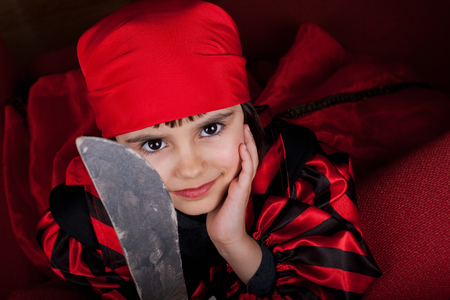 Portrait of a little girl dressed as pirate with an old cardboard sword photo