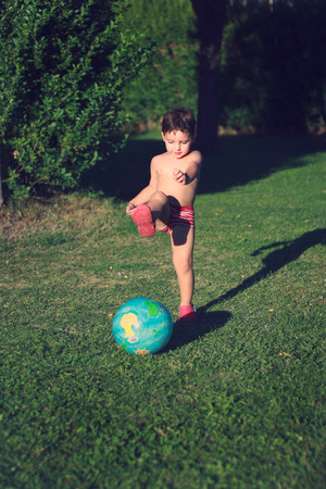 clumsiness: Little boy playing soccer with a globe shaped ball
