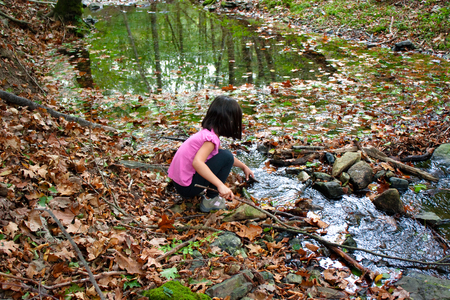 Little girl playing with water in a river in autumn