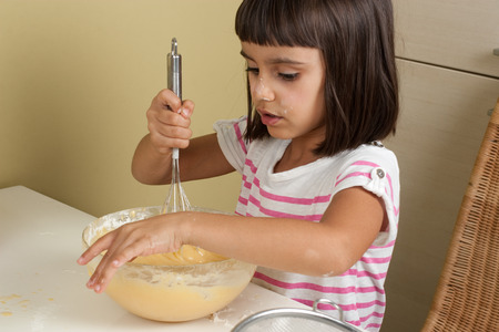 beating: Cute and happy little beating the mixture to cook a cake