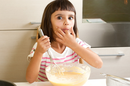 Happy and funny little girl sucking the mixture to cook a cake photo