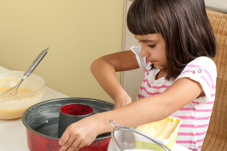greasing: Happy little girl greasing a mold with butter to bake a cake