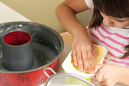 greasing: Happy little girl greasing a mold with hand to bake a cake  Focus on hand into the butter